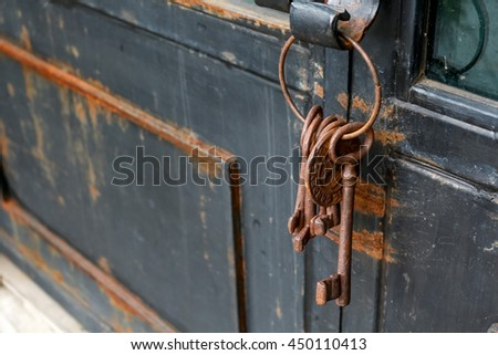 some old and rusty keys chain on a rustic door - stock photo