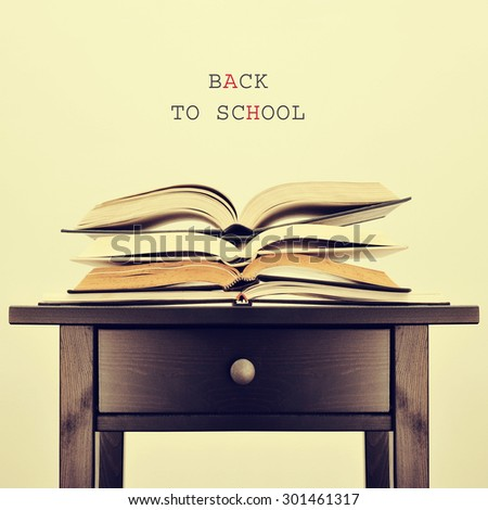 some open books on a table and the sentence back to school on a beige background, with a retro effect - stock photo