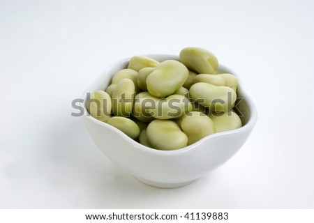 some organic broad beans in a white bowl - stock photo