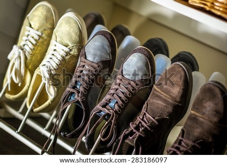 Some pairs of men's shoes on SHOE RACK in the storeroom at home. - stock photo