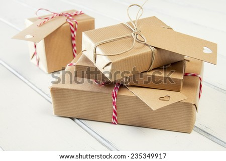 Some paper parcels wrapped tied with tags. Christmas gift boxes wrapped with paper kraft and tied with red & white baker's twine on a white wooden table. Vintage Style. - stock photo