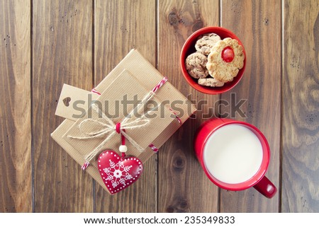 Some paper parcels wrapped tied with tags. Cookies, a milk mug for Santa, a red heart and christmas gift boxes with paper kraft and tied with red & white baker's twine on a wooden table. Vintage Style - stock photo