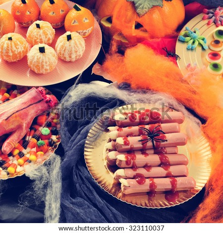 some plates with different Halloween food, such as candies, scary fingers or mandarines as pumpkins, with different scary ornaments as an amputated hand, spiders and cobwebs - stock photo