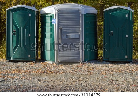 Some portable toilets located on the wooded hiking trail. - stock photo