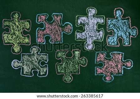 some puzzle pieces drawn with chalk of different colors on a green chalkboard, as the symbol for the autism awareness - stock photo