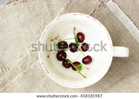 Some ripe dark red cherry in a vintage white cup on rough linen cloth. Amazing beautiful composition with romantic summer theme in a rustic setting. Shabby chic - stock photo