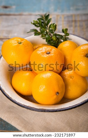 some ripe fresh mandarins in dish on wooden background - stock photo