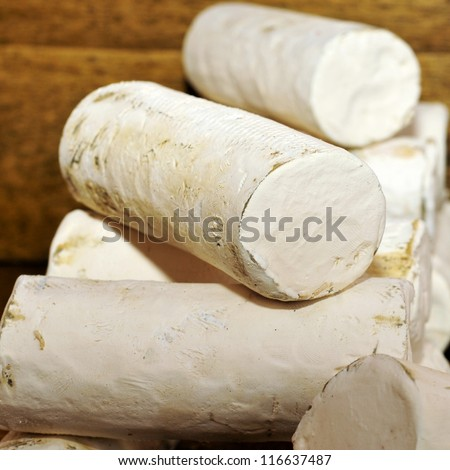 some rolls of artisan goat cheese in a market stall - stock photo