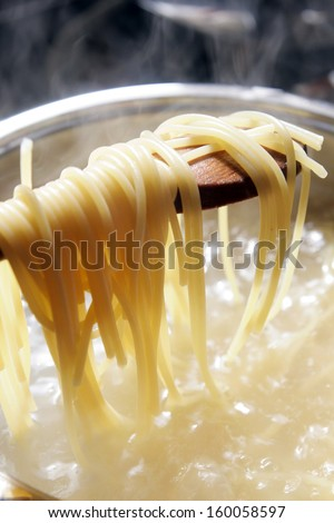 Some spaghetti are cooking in hot water - stock photo