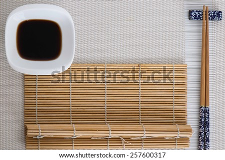 Some sushi tools set on white background and a bamboo mat - stock photo