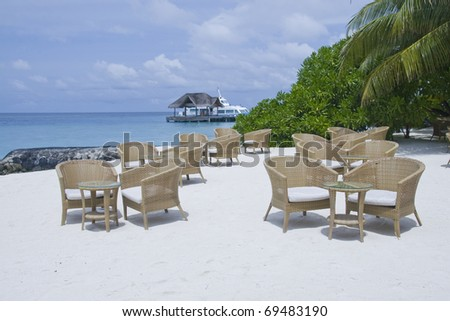 Some tables and chairs in a cafe on the beach in maldives - stock photo