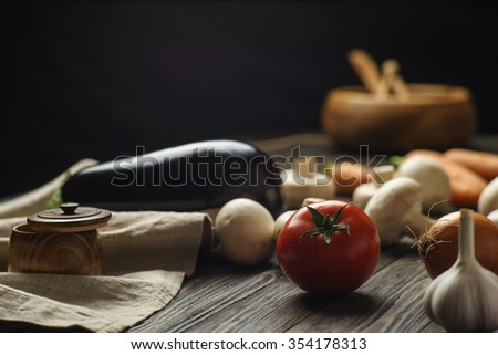 Some vegetables and mushrooms on brushed wooden table on a dark background - stock photo