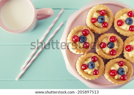 Some vol-au-vent with blueberries and red currants on a cake stand and a mug of milk on a robin egg blue wooden table. Vintage Style. - stock photo