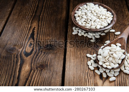 Some White Beans on a rustic wooden background (close-up shot) - stock photo