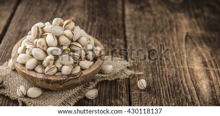 Some whole Pistachios (selective focus; close-up shot) on wooden background - stock photo