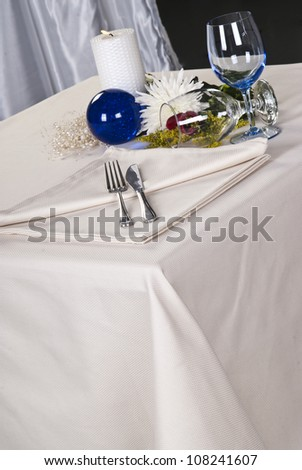 Some wine glasses on a festive table arranged with burning candle. - stock photo