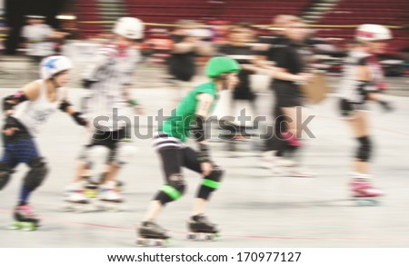 some women participating in roller derby with a motion blur - stock photo