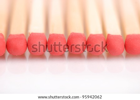 some wooden matches in line over white background/matches with the reflection - stock photo