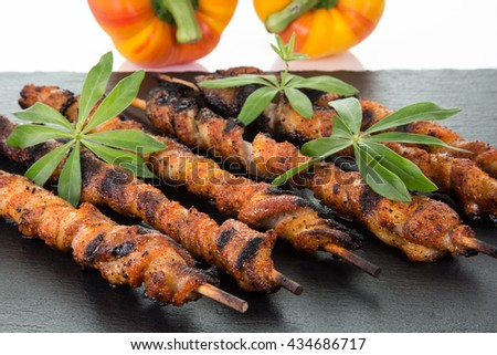 Some wrapped meat spits on a slate decorated with two paprika, isolated on white with copyspace. - stock photo