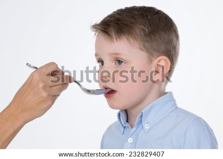 someone gives medicine to a sick kid - stock photo