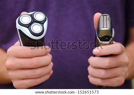 Someone holding up two different types of razors  - stock photo