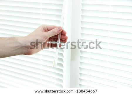 Someone opens blinds - stock photo
