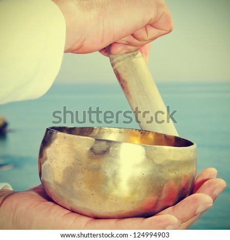 someone playing a tibetan bowl in front of the sea - stock photo
