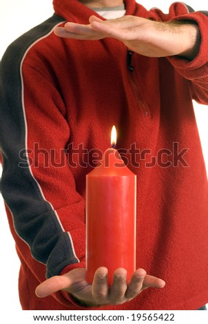 Someone warming their hand over a candle - stock photo