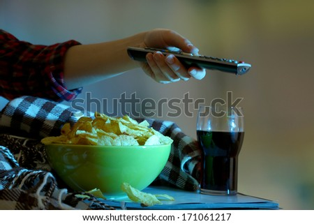 Someone watching TV with crisps and cola in room  - stock photo