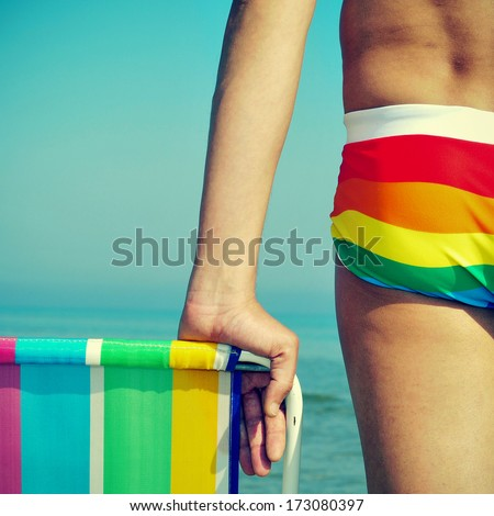 someone wearing a rainbow swimsuit and a colorful deck chair on the beach - stock photo