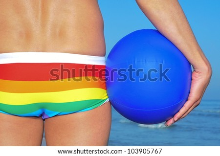 someone wearing a rainbow swimsuit on the beach holding a beach ball - stock photo