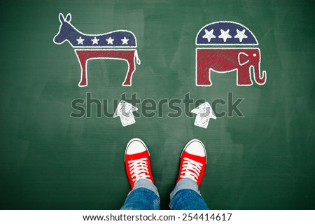 Someone wearing red sneakers choosing between democrats and republicans - stock photo