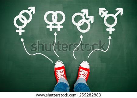 Someone wearing red sneakers choosing between genders - stock photo