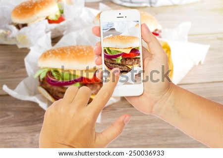 someones hands with mobile phone making  photo of hamburgers - stock photo