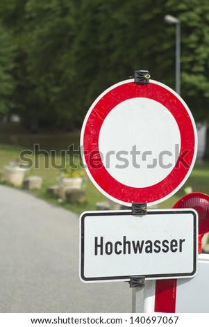 Somewhat worn down German road block sign, warning of a flooded area ahead. Very shallow depth of field for generic usability. - stock photo