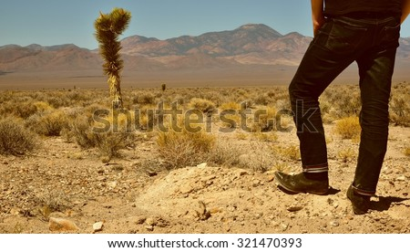 Somewhere in Nevada: Western-style colorized shot of very lonesome guy in cowboy boots standing in the desert. - stock photo