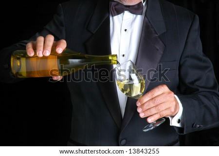 Sommelier in Tuxedo Pouring White Wine from a Bottle into Wine Glass - stock photo