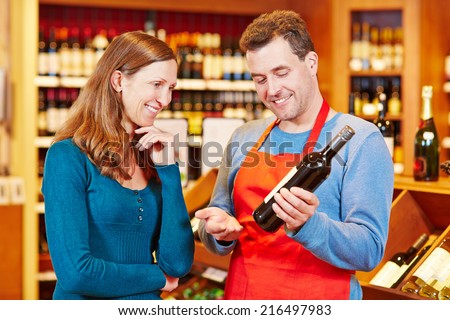 Sommelier in wine store giving woman recommendation for bottle of wine - stock photo