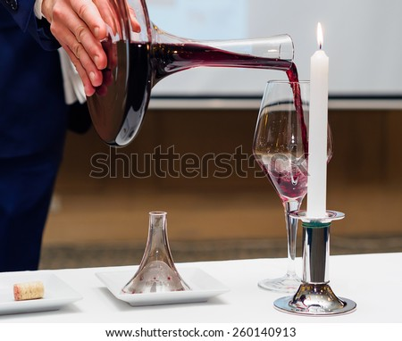 Sommelier pouring wine to glass - stock photo