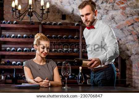 Sommelier pouring wine to the glass with woman in the cellar. Wine degustation - stock photo