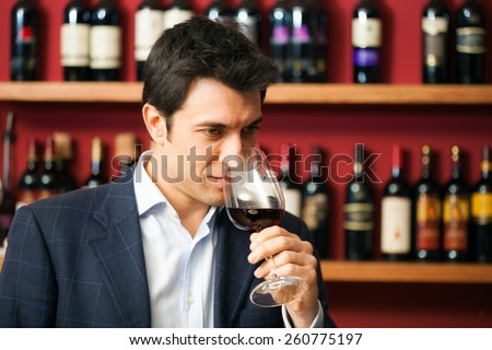 Sommelier tasting a glass of red wine - stock photo