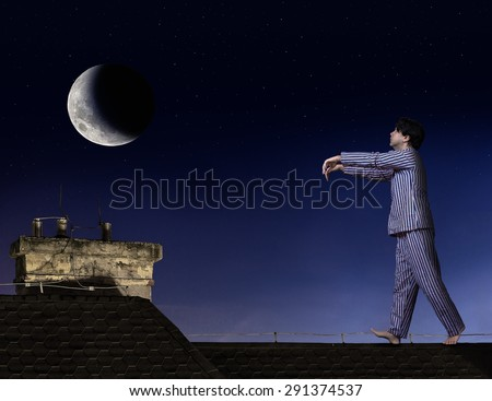 Somnambulist walking on the roof. Man in pajamas walks on roof with outstretched hands. Moony in pajamas walks at night on roof of a house under moonlight. Sleepwalker walk under the moon. - stock photo