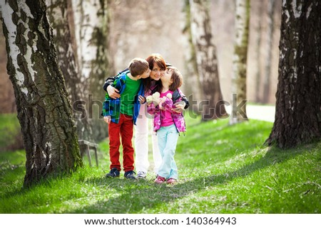 Son and daughter kissing mother while walking along a tree lined path. - stock photo