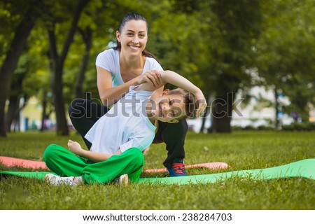 son and mother are doing exercises in the park - stock photo