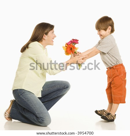 Son giving bouquet of flowers to mother. - stock photo