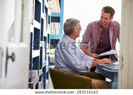 Son Giving Senior Parent Financial Advice In Home Office - stock photo