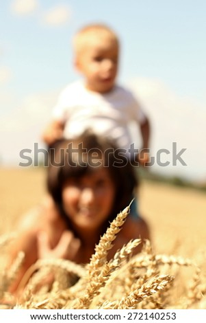 Son in his mothers arms on the field (Shallow DOF). - stock photo
