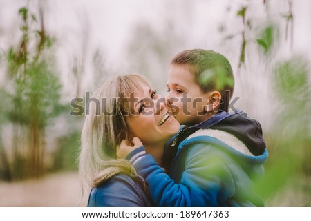 Son is kissing his mother outdoor - stock photo