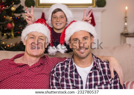 Son joking to his father and grandfather at home in the living room - stock photo