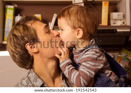 son kissing his father - stock photo